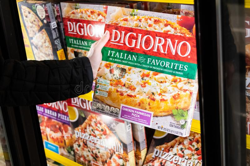 Customer holding a box of Di Giorno brand frozen pizza royalty free stock images