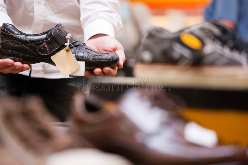 Customer Holding Fashionable Shoe at Supermarket stock images