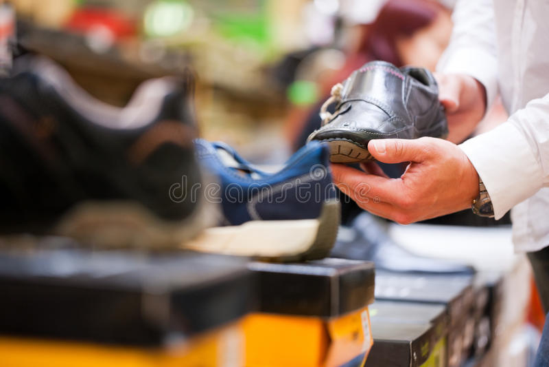 Customer Holding Formal Shoe at Supermarket royalty free stock image