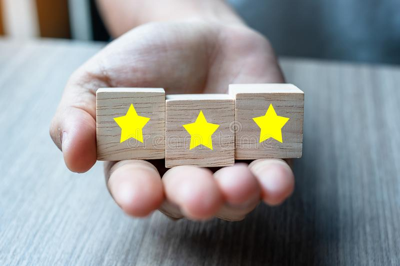 Customer holding wooden blocks with the three star symbol. Customer reviews, feedback, rating, ranking and service concept.  stock image