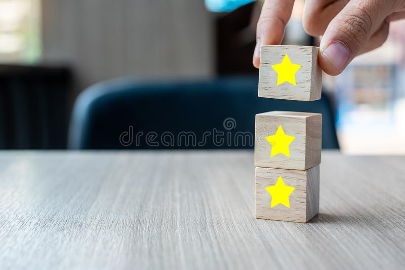 Customer holding wooden blocks with the three star symbol. Customer reviews, feedback, rating, ranking and service concept.  stock photography