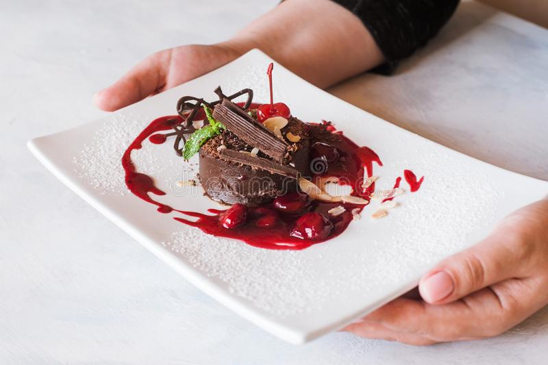 Customer holds chocolate cake with cherry jam. Decorated by sweet red berry, almond and mint. Delicious dessert serving in restaurant royalty free stock photos