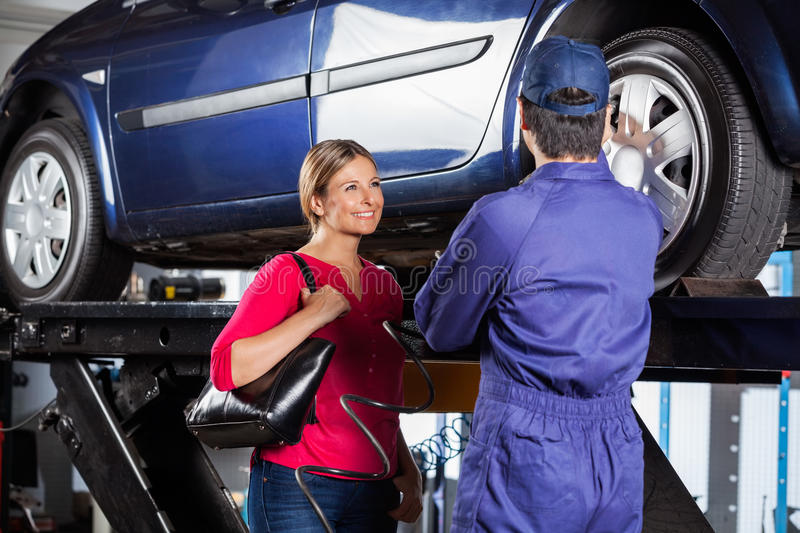 Customer looking at mechanic refilling car tire stock for Garage happy car