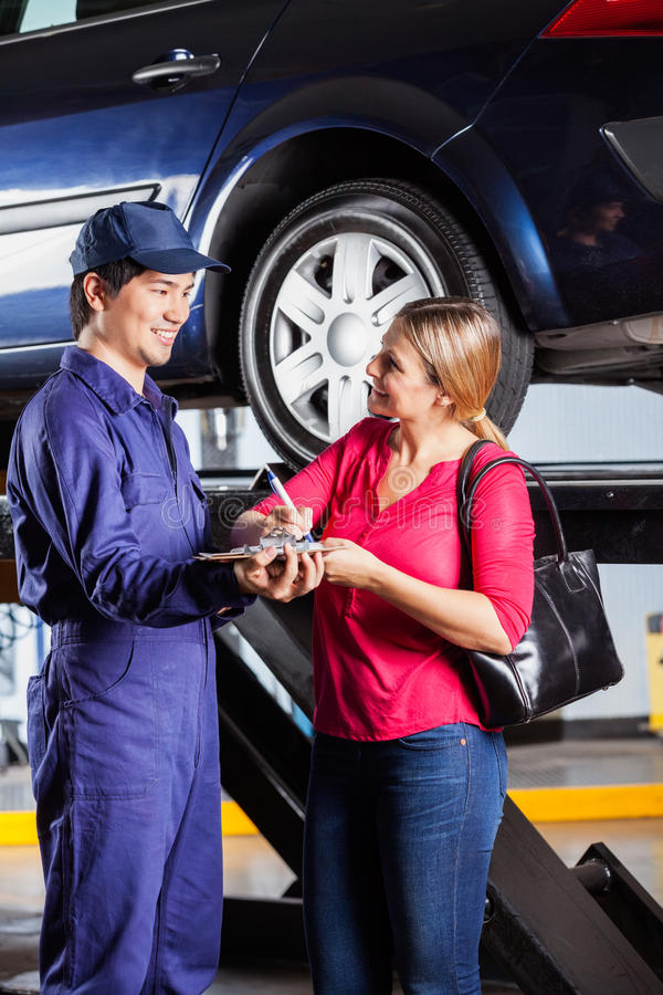 Customer Looking At Mechanic While Signing royalty free stock photo