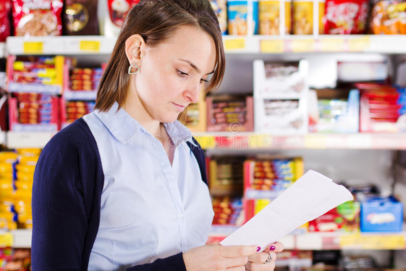 Customer looking at shopping list royalty free stock photography