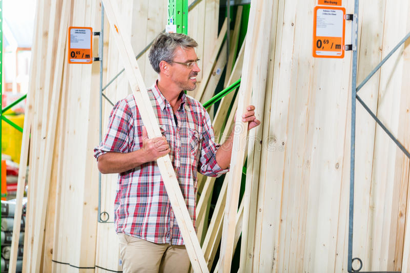 Customer in lumber department of hardware store. Choosing wood strip for DIY-project royalty free stock photos