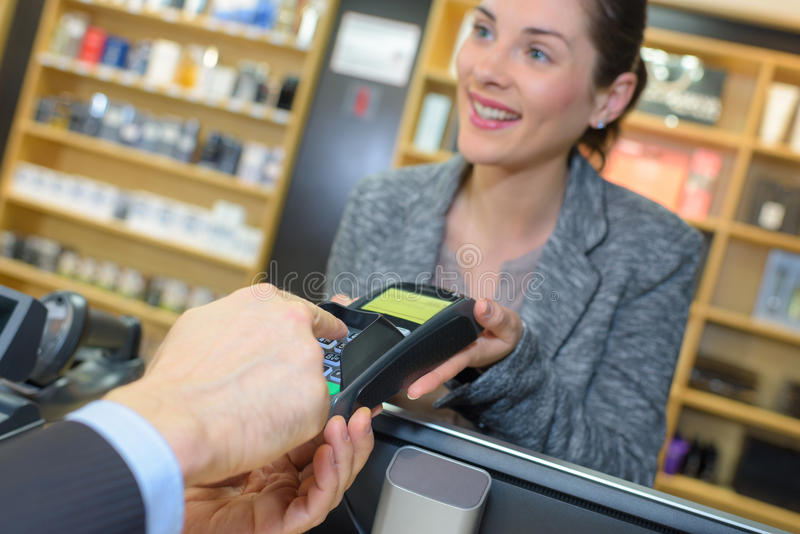 Customer making payment through smartwatch in perfume shop. Customer making payment through smartwatch in the perfume shop royalty free stock photos