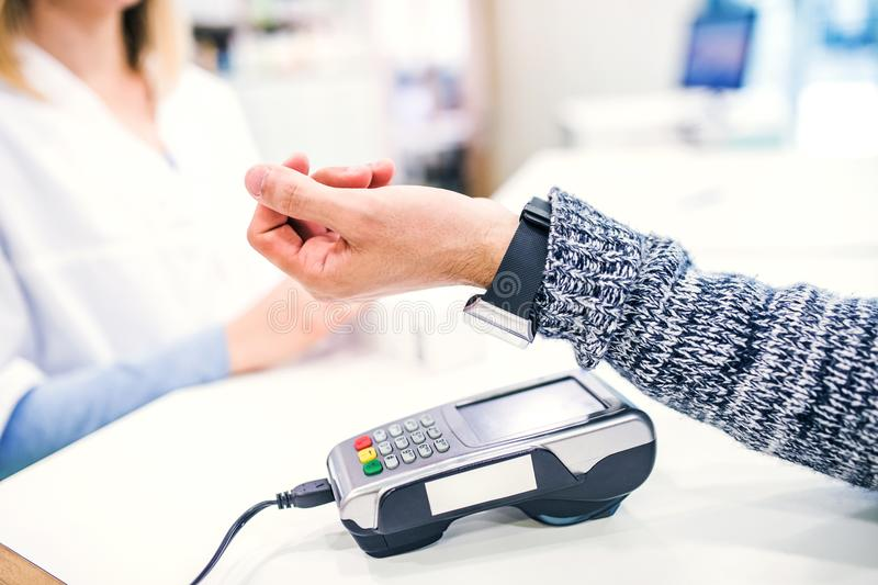 A customer making wireless or contactless payment using smartwatch. An unrecognizable customer making wireless or contactless payment using smartwatch royalty free stock photography