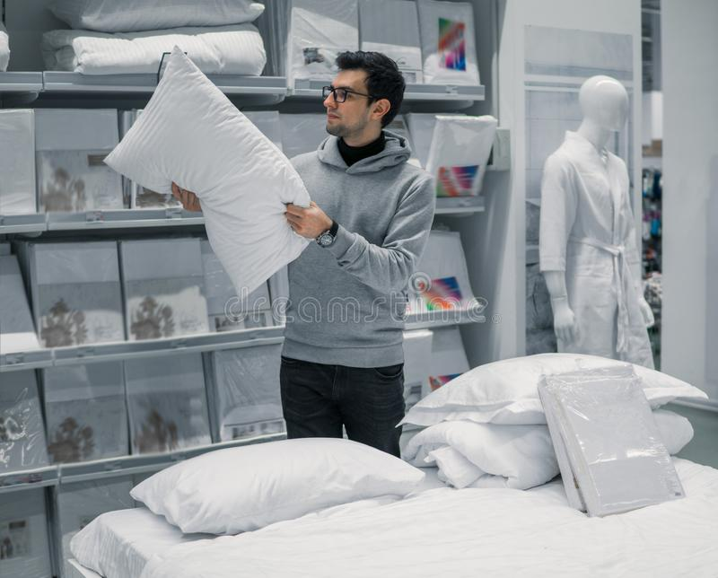 Customer man chooses bed linen in the supermarket mall store. Customer man chooses bed linen and bed in the supermarket mall store. He is j examining one pillow stock photos