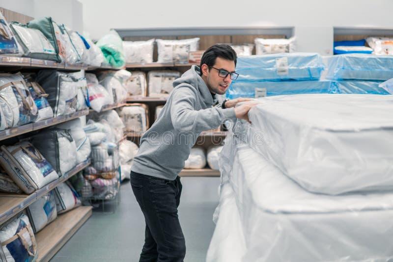 Customer man chooses bed linen in the supermarket mall store. Smart customer man chooses bed linen and bed in the supermarket mall store. He is j examining stock photos