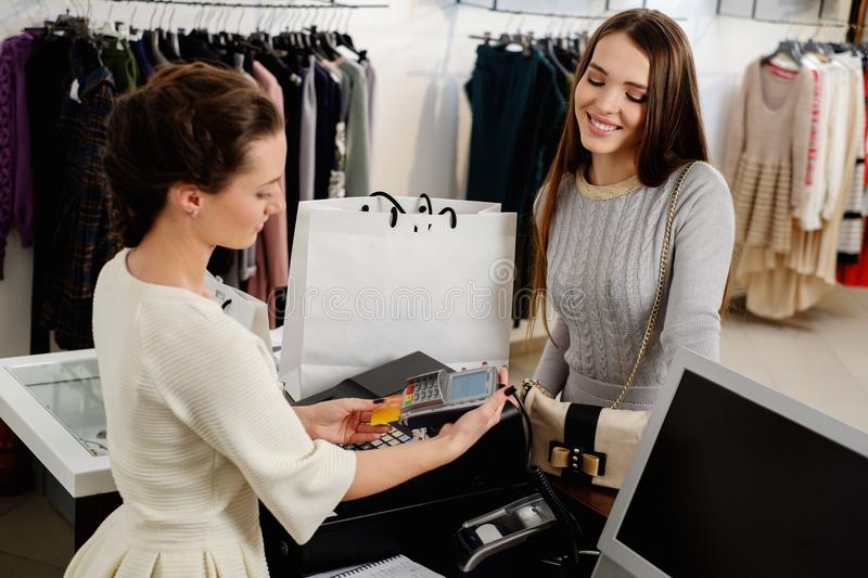 Customer paying with card in a showroom. Happy women customer paying with credit card in fashion showroom stock photography
