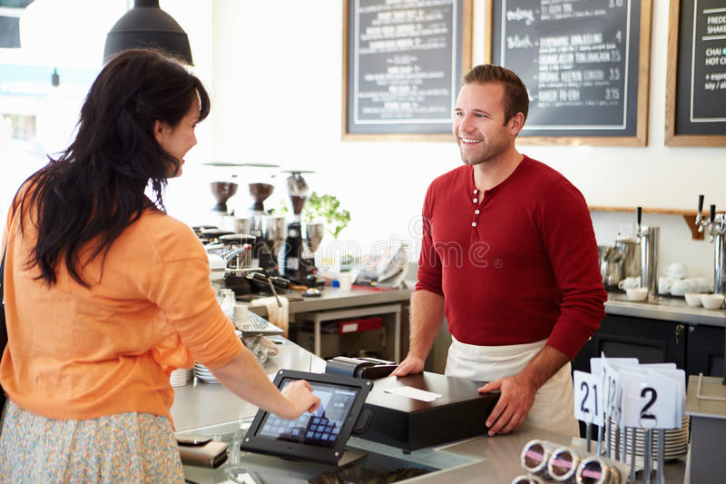 Customer Paying In Coffee Shop Using Touchscreen stock photography
