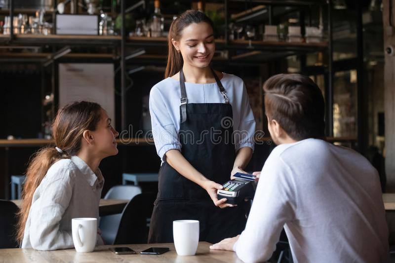 Customer paying by contactless credit card, attractive waitress holding reader. Customer, men paying by contactless credit card with NFC technology in cafe stock photography