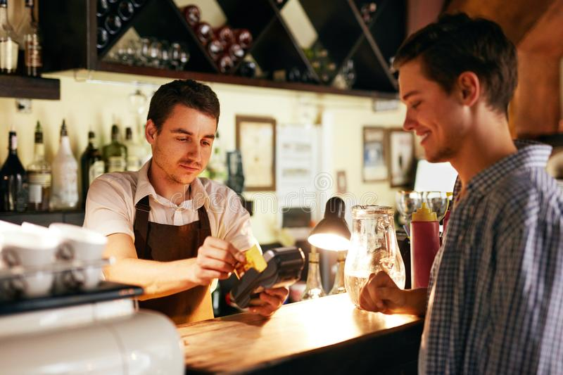 Customer Paying With Credit Card In Cafe stock photos