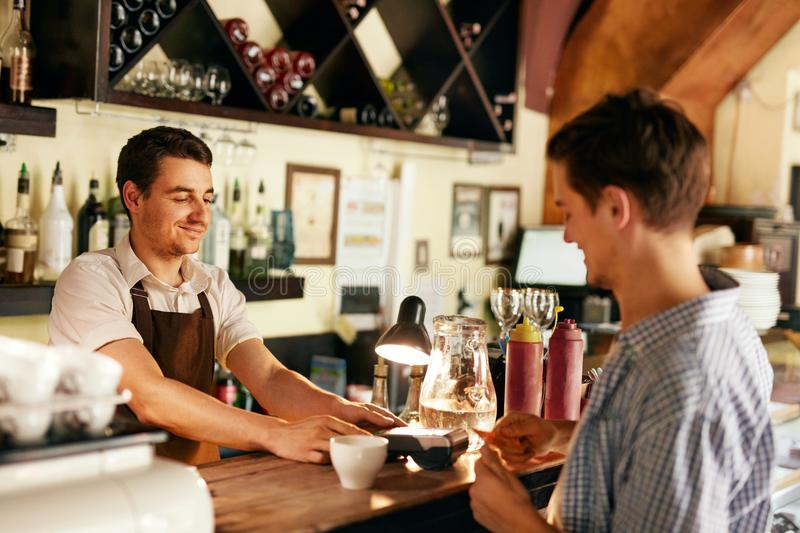 Customer Paying With Credit Card In Cafe stock photography