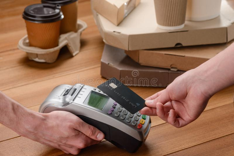 Customer paying for his order. By a credit card, while a vendor holding a terminal. Buying fast food with contactless payments royalty free stock images