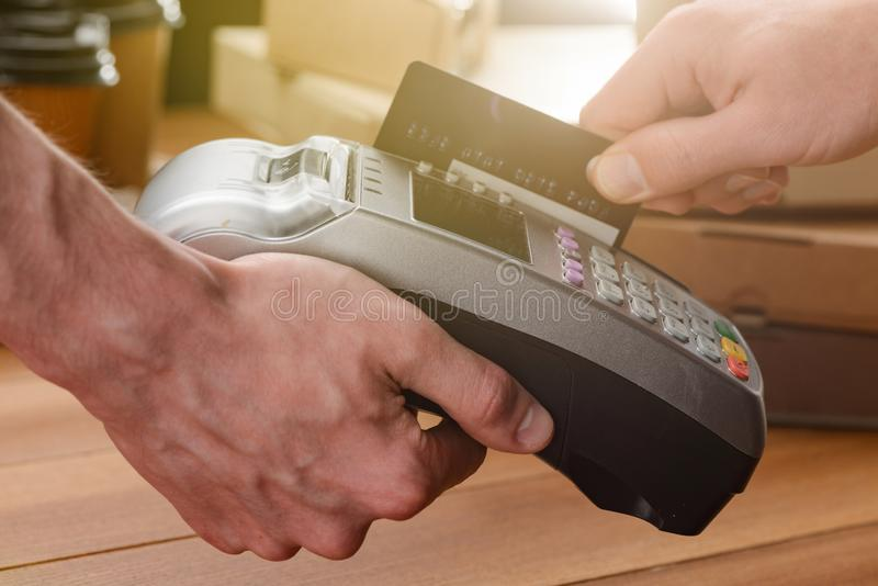 Customer paying for his order. By a swipe card. Easy and secure payment system for small business stock photography