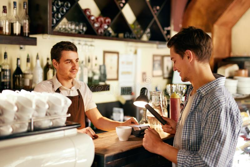Customer Paying With Mobile Phone In Cafe stock images