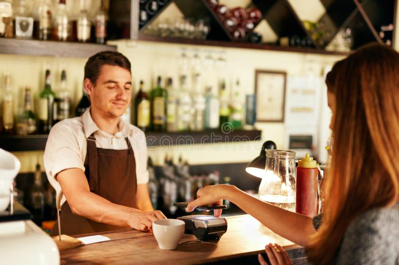 Customer Paying With Mobile Phone In Cafe royalty free stock image