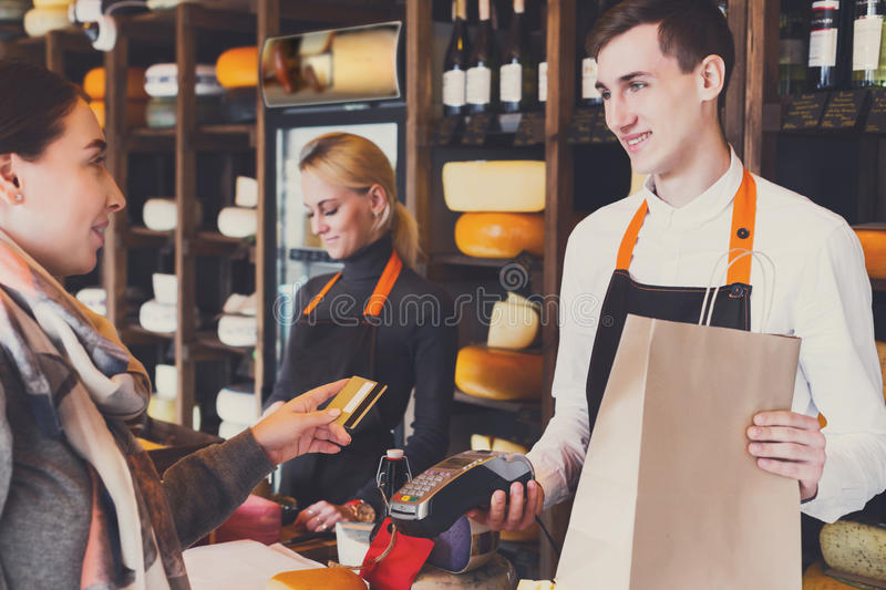 Customer paying for order of cheese in grocery shop. Retail, credit card payment service. Customer paying for order of cheese in grocery shop stock photography
