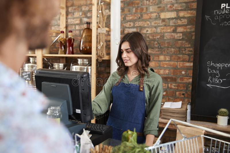 Customer Paying For Shopping At Checkout Of Sustainable Plastic Free Grocery Store royalty free stock images
