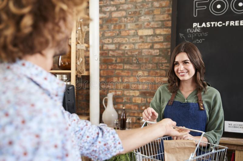 Customer Paying For Shopping At Checkout Of Sustainable Plastic Free Grocery Store royalty free stock photo