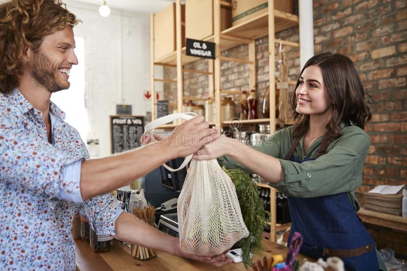 Customer Paying For Shopping At Checkout Of Sustainable Plastic Free Grocery Store royalty free stock photos