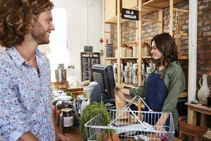 Customer Paying For Shopping At Checkout Of Sustainable Plastic Free Grocery Store stock images