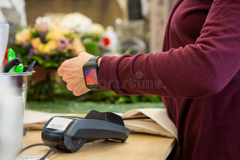 Customer Paying Through Smart Watch At Flower Shop. Cropped image of female customer paying through smart watch at flower shop royalty free stock image