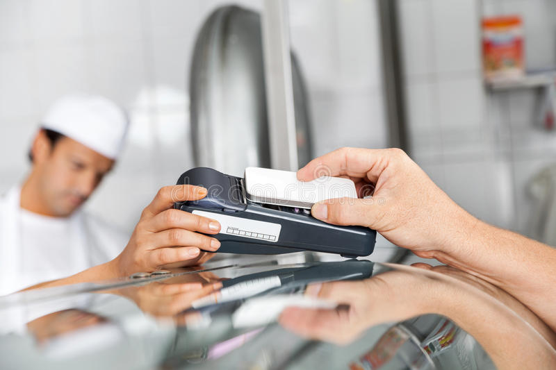 Customer Paying Through Smartphone In Butchery. Cropped image of male customer paying through smartphone in butchery stock photo