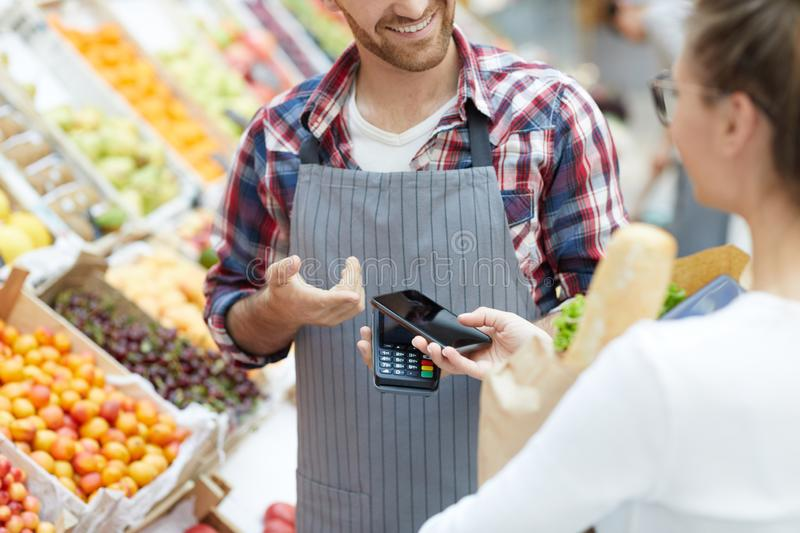 Customer Paying by Smartphone in Supermarket. Mid section portrait of young women paying via smartphone while grocery shopping in supermarket, copy space stock photography