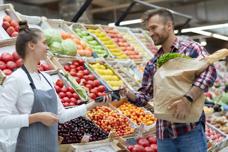 Customer Paying by Smartphone in Supermarket. Side view portrait of handsome young men paying via smartphone at farmers market, copy space royalty free stock photo
