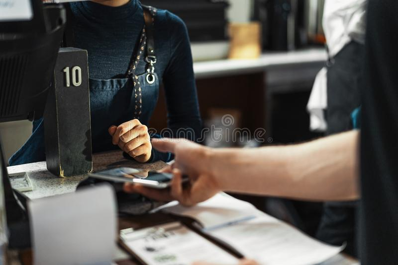 Customer paying via modern payment terminal using mobile phone. NFC payment. stock photos