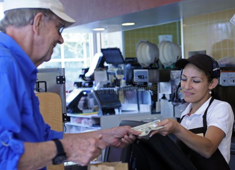Customer pays cashier. Man hands money to cashier to pay for his purchase stock image