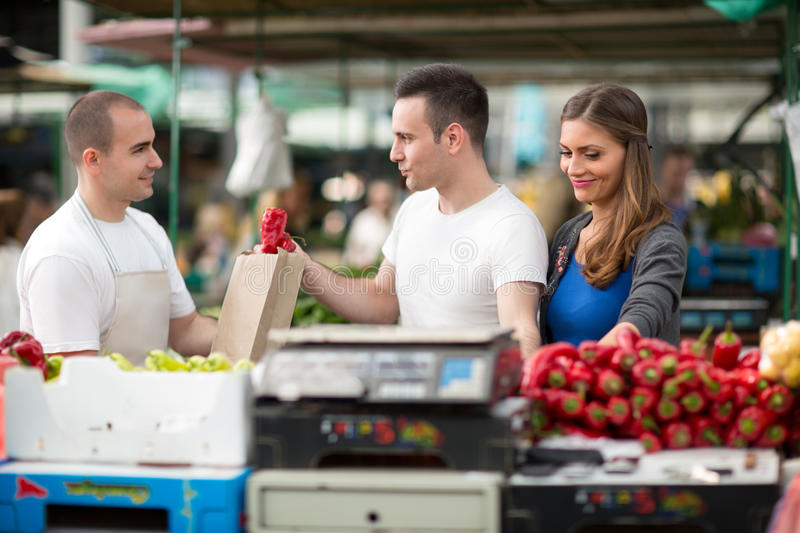 Customer picking pepper from salesman at street market royalty free stock photography