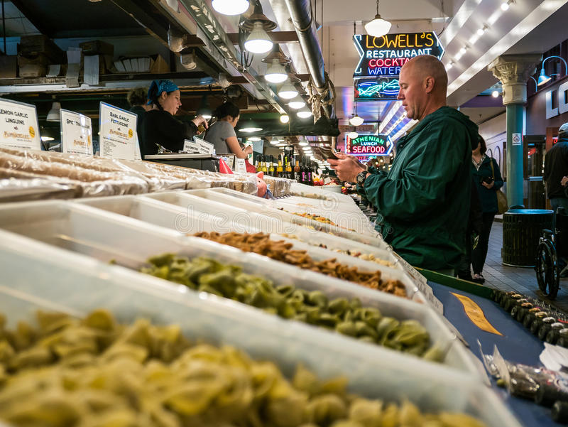 Customer pulls credit card from wallet in front of pasta display stock image