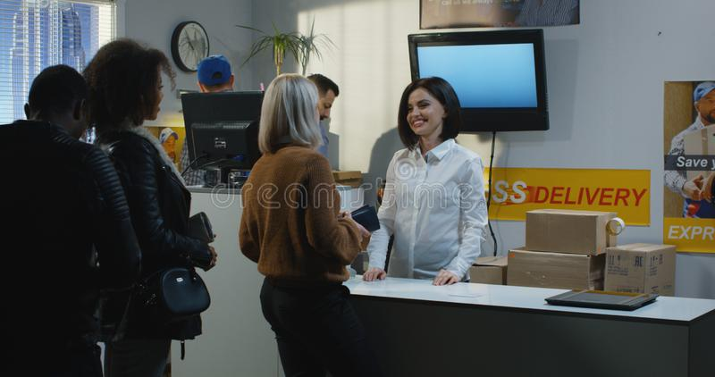 Customer receiving damaged package at customer service desk. Medium shot of a female customer receiving damaged package at customer service desk royalty free stock images