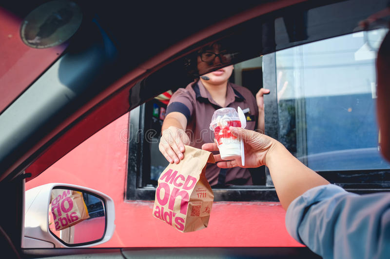 Customer receiving hamburger and ice cream after order and buy it from McDonald`s drive thru service stock image