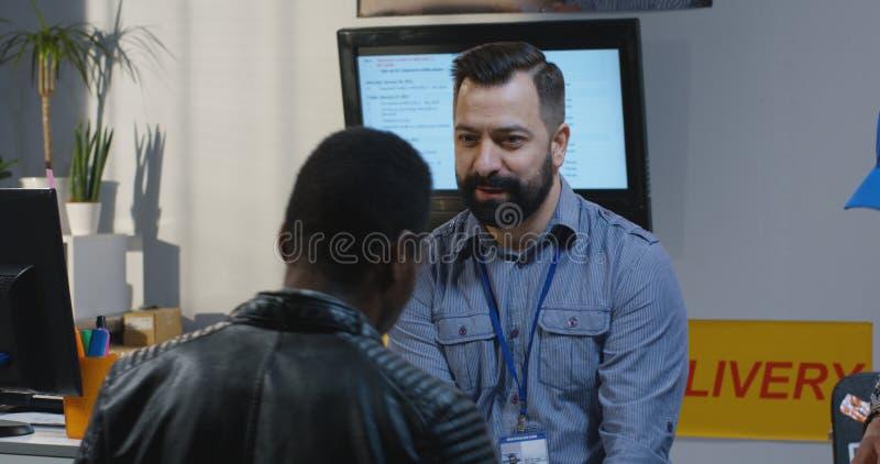 Customer receiving package at a customer service desk. Medium shot of a male customer receiving a package at a customer service desk stock images