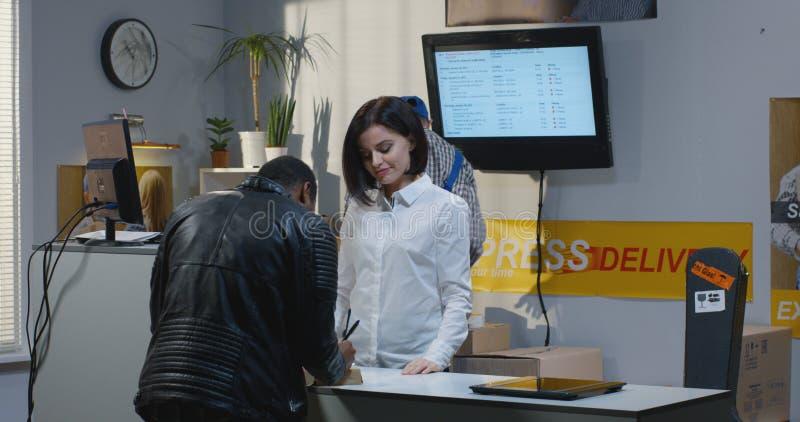 Customer receiving package at a customer service desk. Medium shot of a male customer receiving a package at a customer service desk stock photos
