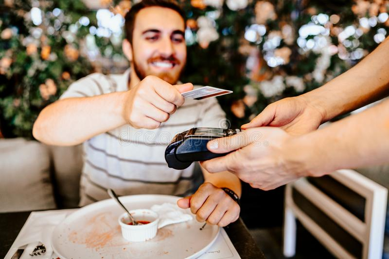 Smiling customer at restaurant paying for lunch with contactless credit card. Contactless technology details royalty free stock images