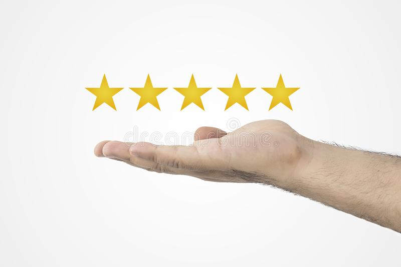 Customer review concept.. Rating golden stars. Feedback, reputation and quality concept. Hand holding golden five star rating. stock image