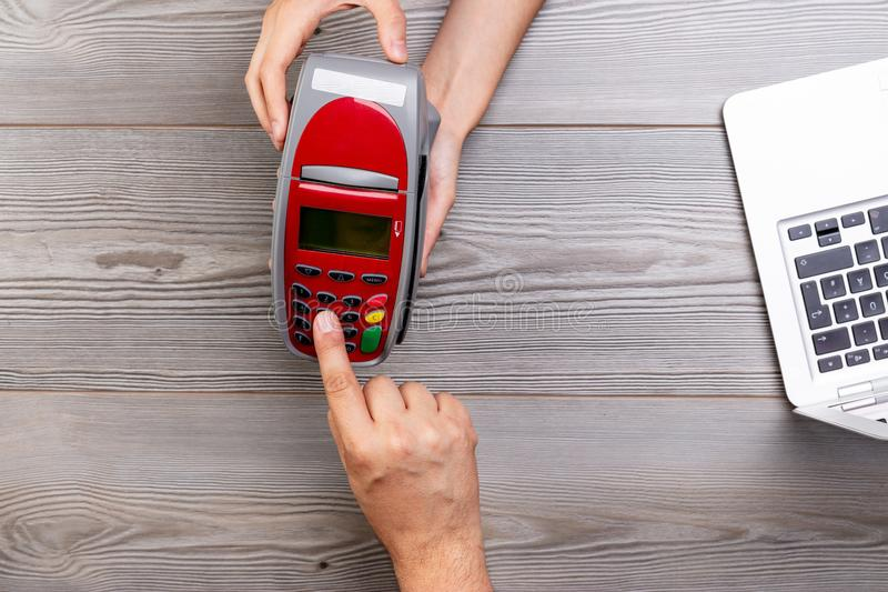 Customer dialing pin code on payment terminal. Customer`s hand dialing his card pin code on a payment terminal brought by the seller stock image
