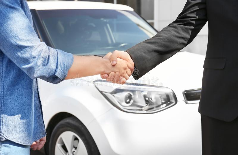 Customer and salesman shaking hands near new car stock images