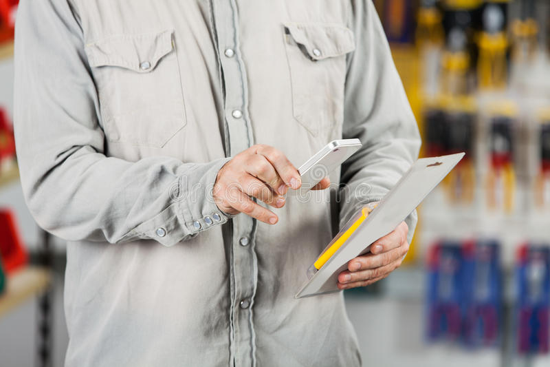 Customer Scanning Tool Packet Through Mobilephone. Midsection of male customer scanning tool packet through mobilephone in hardware store royalty free stock image