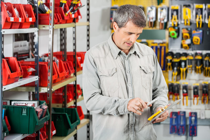 Customer Scanning Tool Packet Through Smartphone. Mature male customer scanning tool packet through smartphone in hardware store royalty free stock photography