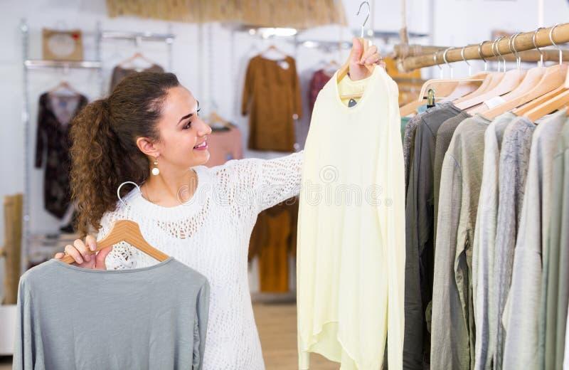Customer selecting basic garments. Brunette female customer selecting basic garments at the store royalty free stock photo