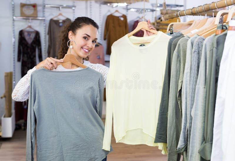 Customer selecting basic garments. Brunette female customer 25-35 years old selecting basic garments at the store stock photos