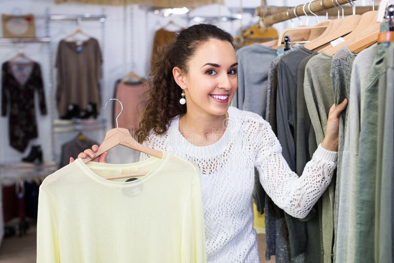 Customer selecting basic garments. Brunette happy customer selecting basic garments at the store royalty free stock photo