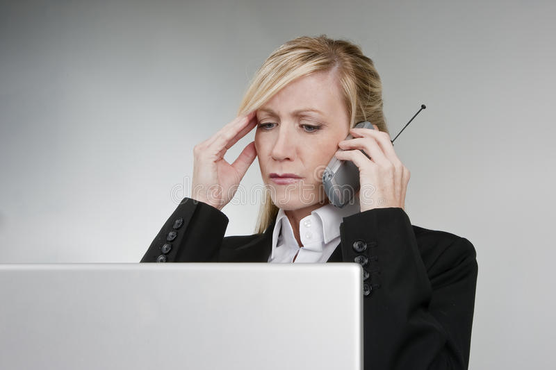 Customer Service. A female customer service agent shows her frustration with the telephone and computer stock image